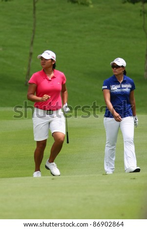 KUALA LUMPUR, MALAYSIA - OCTOBER 16: Yani Tseng and Se Ri Pak (blue) walk towards the green of hole #18 on day 4 of the Sime Darby LPGA 2011 golf tournament on Oct 16, 2011 in Kuala Lumpur, Malaysia. - stock photo
