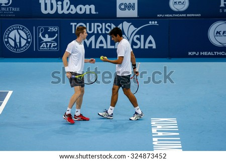 KUALA LUMPUR, MALAYSIA - SEPTEMBER 30, 2015: Jonathan Marray (left) and Rameez Junaid (right) reacts after a point their match at the Malaysian Open 2015 tennis tournament held at the Putra Stadium. - stock photo