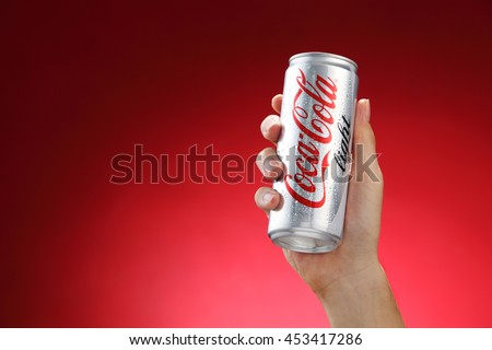 Kuala Lumpur,Malaysia 11th July 2016, Hand hold a can Coca-Cola light on red background. Coca Cola drinks are produced and manufactured by The Coca-Cola Company.
