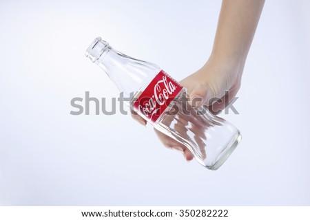 kuala lumpur-malaysia, 16th november 2015, female hand holding  empty  coca cola glass bottle - stock photo