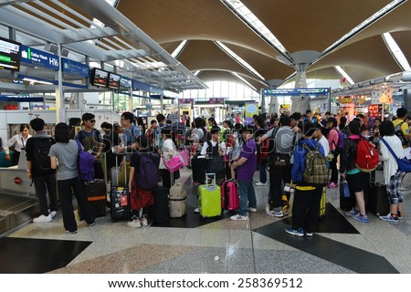 KUALA LUMPUR - MAR 2: Travellers queue to check-in at Kuala Lumpur International Airport (KLIA) on Mar 2, 2014 in Kuala Lumpur, Malaysia. KLIA has the capacity to carry 70 million passengers per year. - stock photo