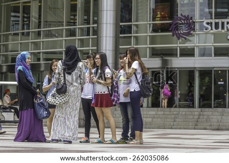 KUALA LUMPUR - March 01, 2015: Undefined tourists taking pictures on Suria KLCC in Petronas Twin Towers background on March 01, 2015 in Kuala Lumpur.  - stock photo