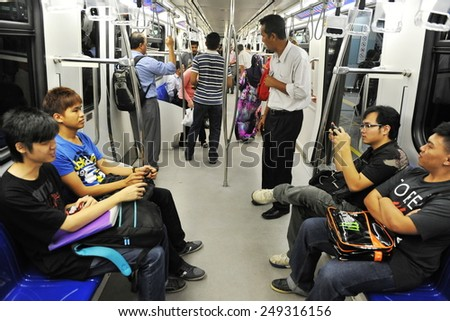 KUALA LUMPUR - MAY 13: Commuters travel on a city subway train on May 13, 2013 in Kuala Lumpur, Malaysia. The Malay capital was founded in 1859 and is now home to over 1.6 million people. - stock photo