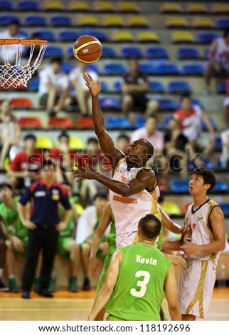 KUALA LUMPUR - OCTOBER 28: Farmcochem's Chris Kuete rolls the ball to the hoop in a Malaysia National Basketball League match against Crouching Tiger on October 28, 2012 in Kuala Lumpur, Malaysia. - stock photo