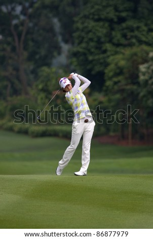 KUALA LUMPUR - OCTOBER 16: Na Yeon Choi of South Korea watches her shot from the fairway of the KL Golf & Country Club at the Sime Darby LPGA 2011 on October 16, 2011 in Kuala Lumpur, Malaysia. - stock photo