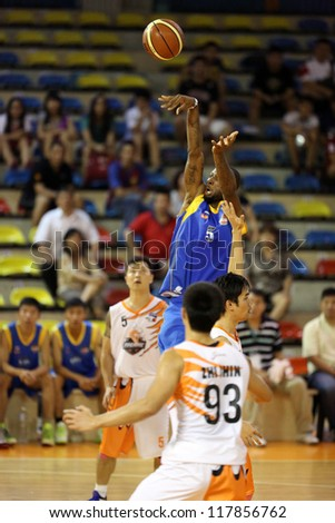 KUALA LUMPUR - OCTOBER 27: Stallion's Emmitt Rimmer #5 shoots over Firehorse's players (white) in a Malaysia National Basketball League match on October 27, 2012 in Kuala Lumpur, Malaysia. - stock photo