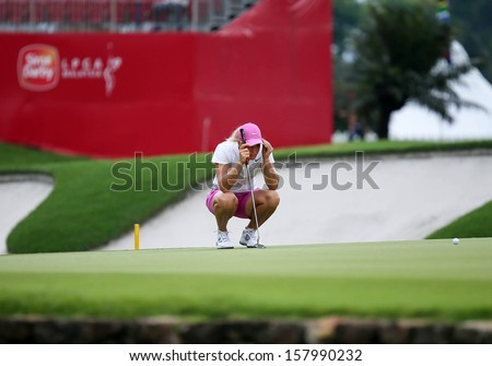 KUALA LUMPUR - OCTOBER 12: Suzann Pettersen of Norway lines up her putt at the 2nd hole green of the KLGCC course on Day 3 of the Sime Darby LPGA on October 12, 2013 in Kuala Lumpur, Malaysia. - stock photo