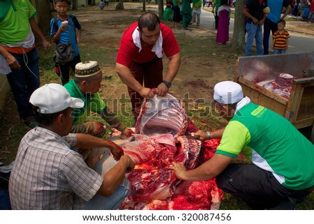 KUALA LUMPUR-SEP 24: An unidentified Malaysian Muslim prepares meat to distribute to the poor & homeless during Eid Al-Adha Al Mubarak,the Feast of Sacrifice September 24 2015 in Kuala Lumpur Malaysia - stock photo
