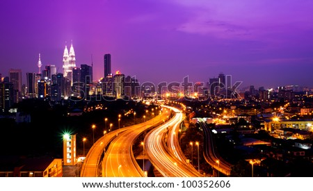Kuala Lumpur twin towers with stunning light trail from the busy highway traffic. - stock photo