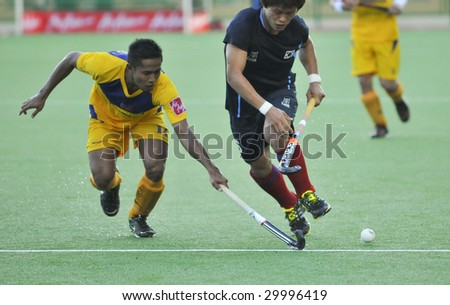 KUANTAN, MALAYSIA - MAY 9 : Korean Lee Nam Yong (R) controls the ball away from Malaysian player at 8th AirAsia Men's Asia Cup 2009 hockey tournament May 9, 2009 in Kuantan, Pahang, Malaysia.