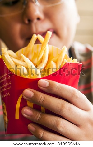 Kuching, Malaysia - June 3, 2015: A hungry kid holding a packet of french fries in McDonald restaurant.