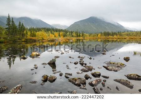 Kuelporr mountain with peak hidden in clouds reflected in shallow Polygonal northern taiga forest lake with lichen-covered rocks in foreground - stock photo