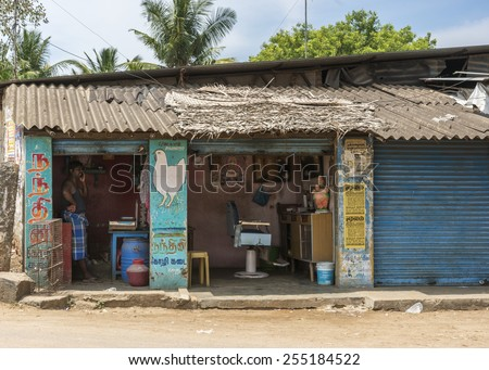 KUMBAKONAM, INDIA - OCTOBER 11, 2013: In rural Tamil Nadu, a chicken butcher is the neighbor of a barber shop.