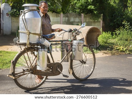 KUMBAKONAM, INDIA - OCTOBER 13, 2013:  Milkman carrying a very large and small milk cans on his rusty bike along a rural road. - stock photo