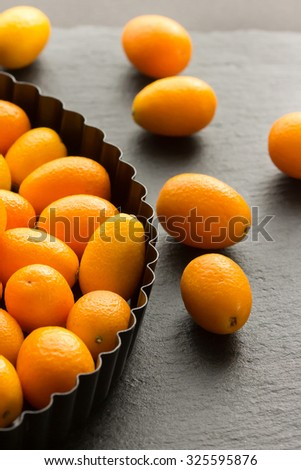 Kumquats on a Plate on a Table - stock photo