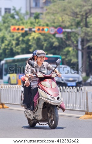 KUNMING, CHINA-JULY 5, 2014. Cheerful woman on electric bike. Many electric bikes in China are the scooter style e-bike that may or may not have pedals. The Chinese e-bike market is the largest in the world. - stock photo