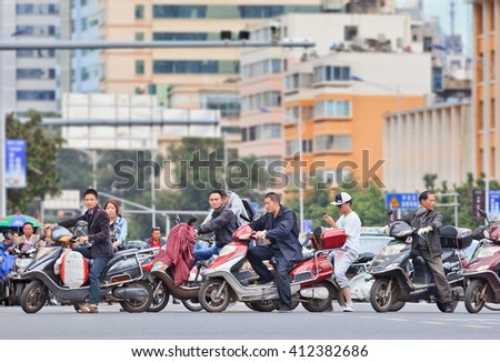 KUNMING, CHINA-JUNE 30, 2014. Men on e-bikes in city center. Many electric bikes in China are the scooter style e-bike that may or may not have pedals. The Chinese e-bike market is the largest in the world. - stock photo