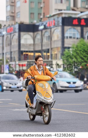 KUNMING, CHINA-JUNE 30, 2014. Woman on yellow electric bike. Many electric bikes in China are the scooter style e-bike that may or may not have pedals. The Chinese e-bike market is the largest in the world. - stock photo