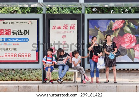 KUNMING-JULY 5, 2014. People at bus stop with advert. China's outdoor advertising market grows annually more than 23% since 2000, versus 17% for overall ad market, 14% for TV and 16% for newspapers. - stock photo