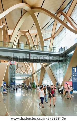 KUNMING-JULY 14, 2014. Spacious interior of Kunming Changshui International Airport with travelers walking around. It is the primary airport serving Kunming, the capital of Yunnan Province, China. - stock photo