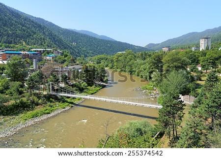 Kura (Mtkvari) river with pedestrian bridge and western suburb of Borjomi, Georgia - stock photo