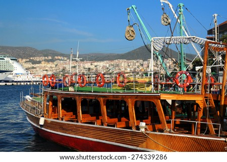 KUSADASI, TURKEY - SEPTEMBER 24, 2009: Recreational boat in the port against the town background. - stock photo