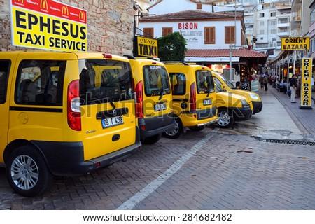 KUSADASI, TURKEY - SEPTEMBER 24, 2009: Yellow cabs at the cab-stand  - stock photo