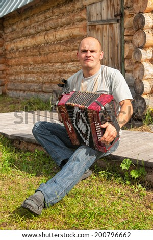 KVAZENGA, ARKHANGELSKY REGION/RUSSIA - JUNE 24: Accordion player sits on decking before barn and plays against blurred background on June 24, 2010 in Kvazenga.