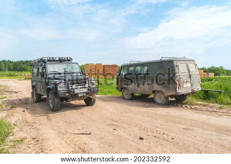 KVAZENGA, ARKHANGELSKY REGION/RUSSIA � JUNE 23: Land Rover Defender SVX 60-year edition and UAZ-452 (Bread loaf) off-road van stand on dirty road before board stack on June 23, 2010 in Kvazenga.  - stock photo