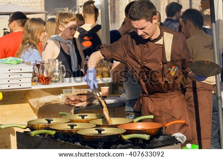 KYIV, UKRAINE - APR 17: Weary cook prepares meat dishes in cast iron pans in outdoor kitchen during Street Food Festival on April 17, 2016. Kiev is the 8th most populous city in Europe. - stock photo