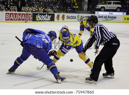 KYIV, UKRAINE - APRIL 23: Dmitri Upper of Kazakhstan (L) fights for a puck with Oleg Shafarenko of Ukraine during their IIHF Ice-hockey World Championship DIV I game on April 23, 2011 in Kyiv, Ukraine - stock photo
