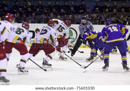 KYIV, UKRAINE - APRIL 18: Referee face-off the rink during IIHF Ice-hockey World Championship DIV I Group B game between Ukraine (in Blue) and Lithuania on April 18, 2011 in Kyiv, Ukraine - stock photo