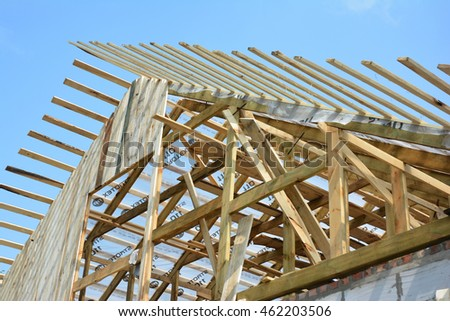 KYIV, UKRAINE - AUGUST 2, 2016: New residential construction home roof framing against a blue sky. Roofing house construction outdoors. Wooden roof construction Exterior.