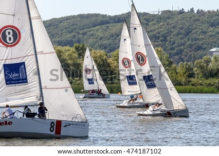KYIV, UKRAINE - AUGUST 26, 2016: Sailing yacht sail in the waters of the Dnieper near the Paton bridge in Kyiv