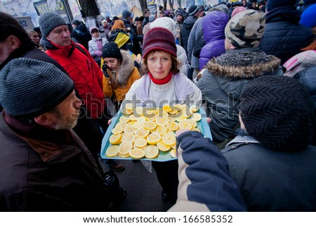 KYIV, UKRAINE - DEC 8: Woman treats demonstrators lemons in the crowd of people on the occupying street during two weeks anti-government protest on December 8, 2013, in Kiev, Ukraine. - stock photo