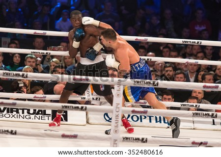 "KYIV, UKRAINE - DECEMBER 12, 2015: Middleweight Dmytro Mytrofanov of Ukraine (blue shorts) fights with Marlo Delgado of Ecuador during ""Evening of Boxing"" in the Palace of Sports in Kyiv - stock photo"