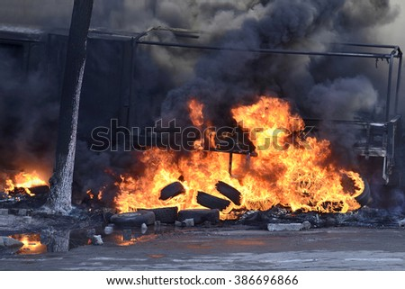 KYIV, UKRAINE - FEBRUARY 18, 2014: The burnt truck and flame of rubber tyres as a protecting of armed special forces attacks.  First day of mass shooting  in events of Euromaydan.