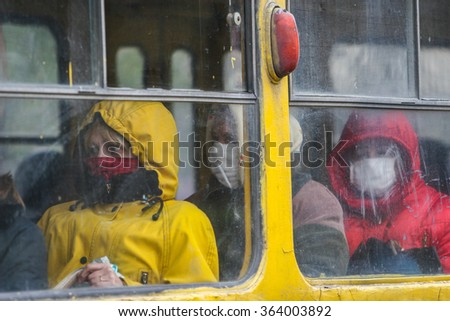 KYIV, UKRAINE - 02.11.2009. Flu epidemic. Passengers travel in transport, covering her face with protective gauze bandages.