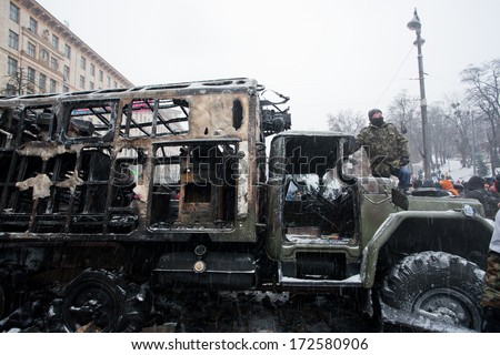 KYIV, UKRAINE - JAN 21: Active protester stands on the burned military auto after fight with police on the street during anti-government riot Euromaidan on January 21, 2014, in Kiev, Ukraine.   - stock photo