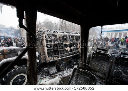 KYIV, UKRAINE - JAN 21: Burned out buses and military auto stand in the occupying street with crowd of protesters during anti-government protest Euromaidan on January 21, 2014, in Kiev, Ukraine - stock photo