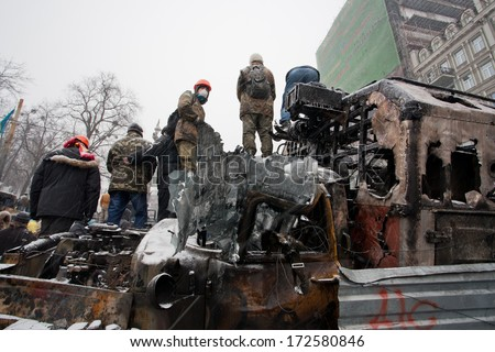 KYIV, UKRAINE - JAN 21: Men in helmets and masks stand on top of broken and burned military cars on occupying winter city during anti-government protest Euromaidan on January 21, 2014 in Kiev, Ukraine - stock photo