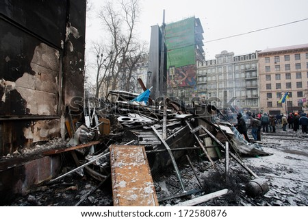 KYIV, UKRAINE - JAN 21: People stand near the burned barricades after night fights on the occupying snow street during anti-government protest Euromaidan on January 21, 2014, in Kiev, Ukraine.  - stock photo