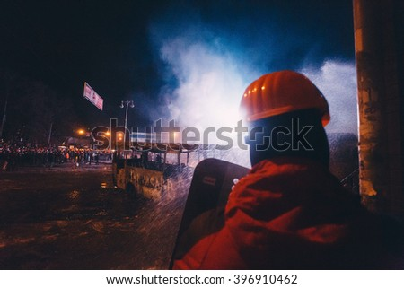 Kyiv, Ukraine - 20 January, 2014: Protester hides from water cannon hiding behind the corner of the building. Police use a water cannon, despite the hard frost. During anti-government protests in Kyiv - stock photo