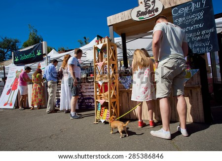 KYIV, UKRAINE - JUNE 6, 2015: Father with a small dog standing in line to fast-food stall of Kiev Food & Wine Festival on June 20, 2014. Kiev is 8th largest city in Europe with population of 2,900,000 - stock photo