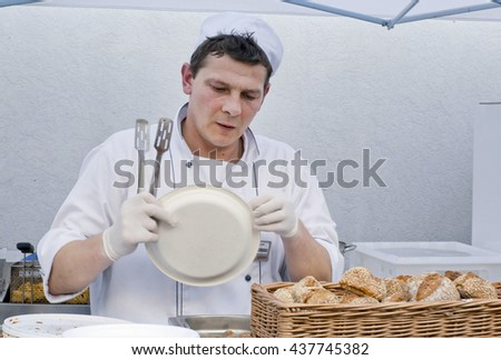 KYIV, UKRAINE - MAY 21: Chef cook in a white dress wants to impose fresh food on a plastic plate inside restaurant kitchen on May 21, 2016. Kiev is the 8th most populous city in Europe. - stock photo