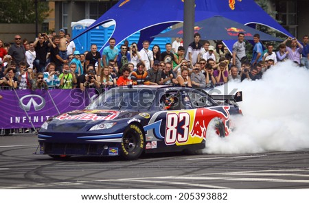 KYIV, UKRAINE - MAY 19, 2012: Daniel Ricciardo of Red Bull Racing Team drives Nascar during Red Bull Champions Parade on the streets of Kyiv city - stock photo