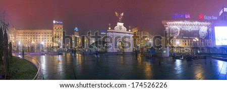 KYIV, UKRAINE - NOV 23, 2013:panorama Independence Square, Maidan area. View of the Arc de Triomphe with a black angel home of Trade Unions and the Post Office ... pedestrians walking in the rain