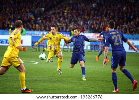 KYIV, UKRAINE - NOVEMBER 15, 2013: Yevhen Konoplyanka of Ukraine (in Yellow) controls a ball during FIFA World Cup 2014 play-off game against France - stock photo