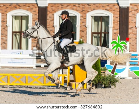 KYIV, UKRAINE - OCTOBER 10, 2015: A participant of competitions in jumping demonstration overcomes obstacle during international equestrian tournament