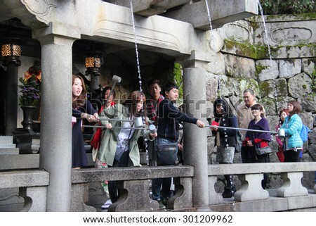Kyoto, Japan - April 11, 2015: Visitors use cups to drink water from 3 streams of Otowa Waterfall at Kiyomizudera wishing in longevity, success in school and a fortunate love life. - stock photo